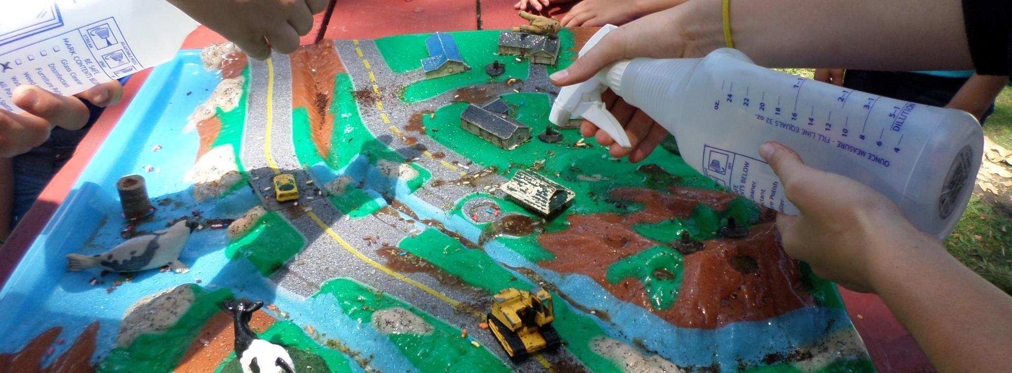 Kids participating in a watershed model demonstration
